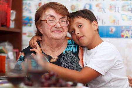 внук: Внук обнимает свою бабушку, глядя на камеру