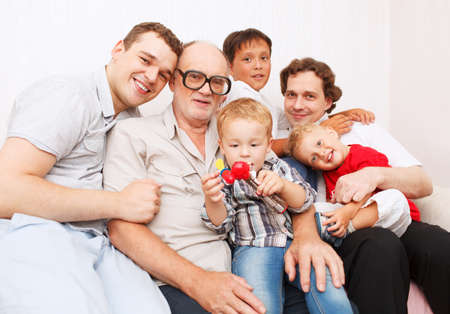 Big family. Generations. Men. Sitting on sofa smiling and looking to the camera. photo