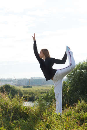 janu: Young woman making asana pose outdoors in the park