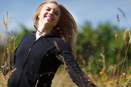 flying woman: Young happy girl of twenty running in the field and laughing