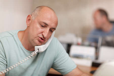 Middle-aged businessman  speaking on the phone and working in the office photo
