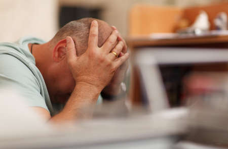depressed man: Worried businessman sitting in front of his computer with his head in his hands Stock Photo
