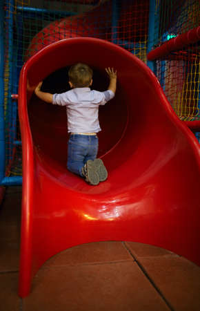 3 year old: 3 year old boy is sitting at the slide hole. Danger. Indoors shot.