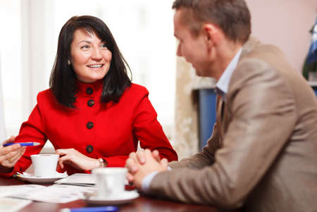 Businesswoman in a meeting with a male colleague smiling at him as they sit at a table discussing paperwork over a cup of coffee