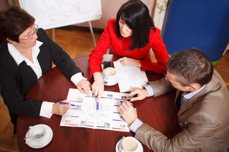 High angle view of a dedicated business team of two women and a man seated at a table having a meeting brainstorming a new project and analysing a document photo