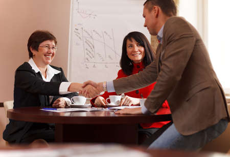 Businessman rising to his feet and shaking hands with a smiling woman executive after a meeting seated around a table as they reach an agreement, congratulate each other or in greeting photo