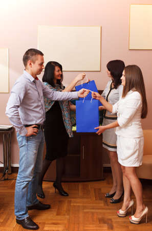 gives: Businessman and woman giving gifts at the office to two stylish young women either to celebrate a holiday such as Christmas or as an award in recognition of an achievement