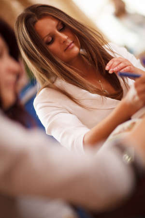 tilted view: Serious beautiful young businesswoman in a meeting writing notes, tilted view past the shoulder of a female colleague Stock Photo