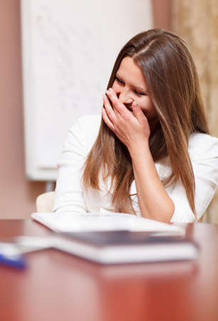 stifle: Businesswoman laughing in a meeting trying to stifle her laughter behind her hand