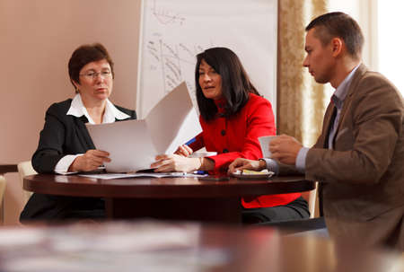 Businesspeople having a meeting over coffee sitting together at a table discussing a document, young man and two middle-aged women present photo