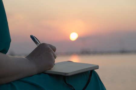 schreibkr u00c3 u00a4fte: Nahaufnahme von der Hand einer Frau schreibt in ihrem Tagebuch bei Sonnenuntergang mit der glühende Kugel von der Sonne reflektiert über ein Stand Ozean Lizenzfreie Bilder
