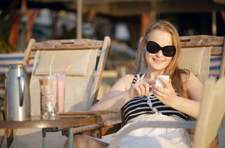 Attractive woman wearing sunglasses relaxing in a deckchair in the sun sending an sms on her mobile phone photo