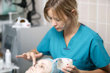 resurfacing: Nurse in a skincare clinic applying protective cream to the delicate skin around the nostrils and eyes of a female patient lying on the surgical couch