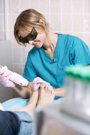 rejuvenate: Podiatrist doing a foot laser treatment on a woman to kill fungal infections of the nail, remove unwanted hair and rejuvenate the skin Stock Photo