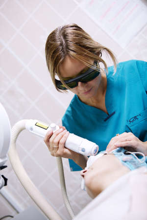 Patient undergoing photorejuvenating skin treatment with a laser administered by a young female clinician for resurfacing the skin to remove solar damage, wrinkles and scars photo