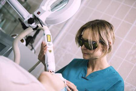 그녀의 피부를 젊어지게 주름 및 흉터를 줄일 수있는 보호 고글 젊은 여성 간호사에 의해 관리 스킨 케어 클리닉에서 레이저 피부 치료를 가진 여자