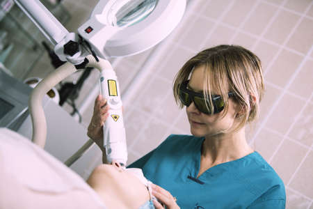 Woman having laser skin treatment in a skincare clinic administered by a young female nurse in protective goggles to rejuvenate her skin and lessen wrinkles and scars