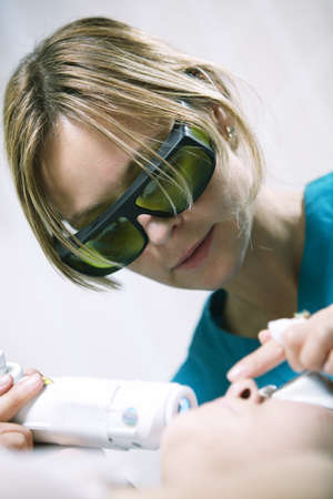 fractional: Doctor or therapist administering fractional skin laser treatment to resurface and rejuvenate a womans skin Stock Photo