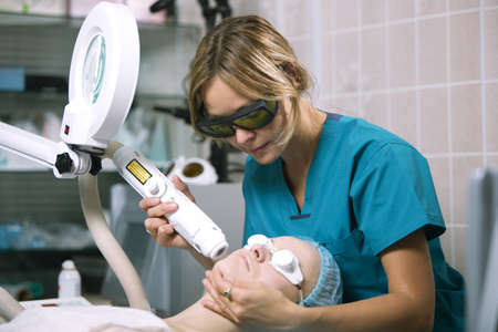 resurfacing: Woman undergoing laser skin treatment or photorejuvenation of the skin on her face in a beauty salon or skin clinic