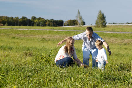 frolic: Protective father playing with his wife and son in a grassy field in open countryside as they laugh and frolic enjoying the fresh air and sunshine Stock Photo