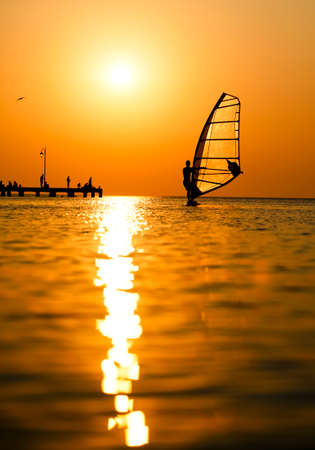 Man passing by with his windsurf or sailboard at sunset on a calm ocean against a spectacular vivid orange sky
