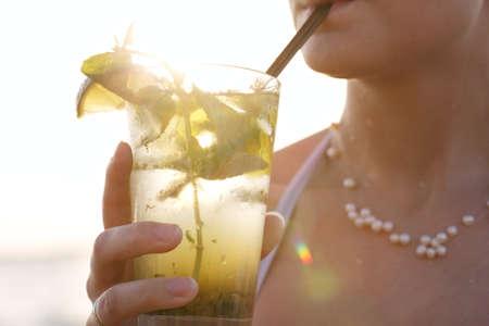 닫기 그녀의 여름 휴가를 빨대로 마시 며 일몰 해변에서 신선한 과일로 장식 열대 모 히 토 칵테일을 즐기는 여자의 닫습니다 스톡 콘텐츠