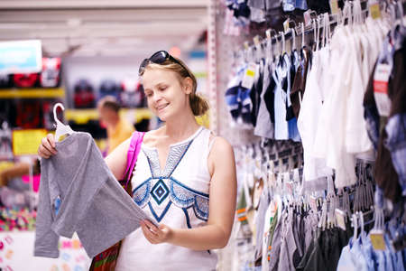 childrens: Attractive young mother shopping for childrens clothes in a retail clothing store viewing items on a rack