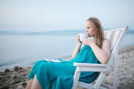 beatitude: Wide shot of young girl enjoying a cup of tea at the seaside sitting relaxing on a deckchair with a blissful expression overlooking a tropical beach Stock Photo