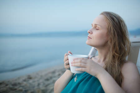 beatitude: Woman with closed eyes enjoying a cup of tea at the seaside sitting relaxing on a deckchair with a blissful expression overlooking a tropical beach