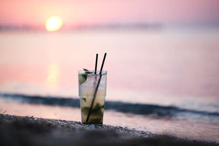 モヒート アルコール カクテルに立っている、熱帯のビーチの砂を下に移動太陽ディスクに対して夕方に日没時のガラスのクローズ アップ