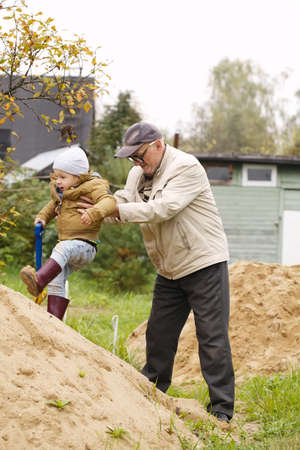 Grandpa helps grandson to get on a sand hill Фото со стока - 26271696