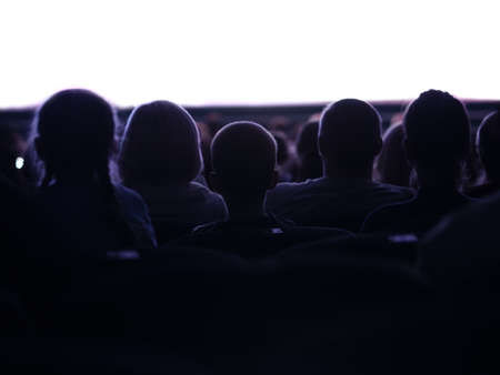 back light: Middle shot of sihouettes of people from back watching cinema or performance with white empty space Stock Photo