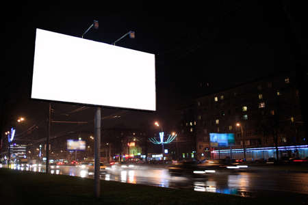 Urban scene with an illuminated empty white billboard on the side of a street with cars in motion and a block of flats in the background, by night