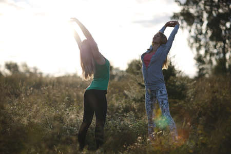 supple: Two young women working out in the garden doing stretching exercises to stay supple and fit