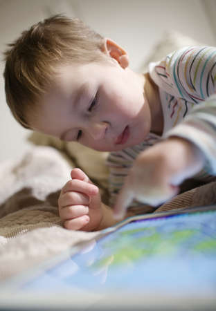 scrolling: Little boy using touchpad and scrolling something there lying on the bed Stock Photo