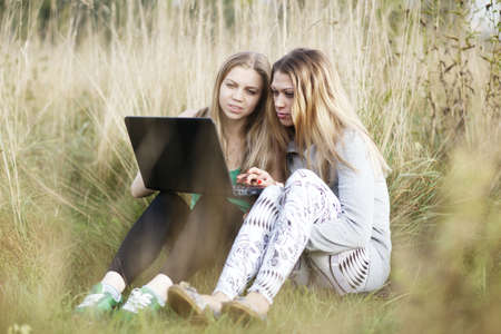 lesbian girls: Two female friends sitting on the grass and talking online using laptop
