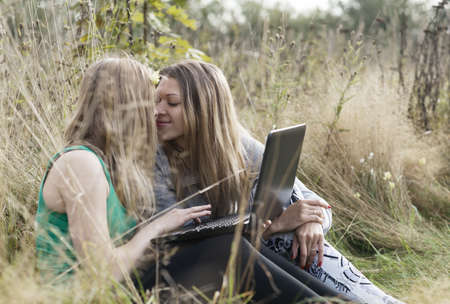 Two women friends sitting close together outdoors with a laptop computer share an intimate moment photo