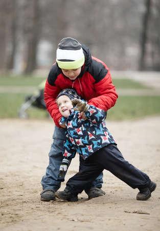 conflictos sociales: Dos jóvenes hermanos jugando al aire libre en un parque en la lucha libre en invierno con los demás, ya que disfrutar de su libertad