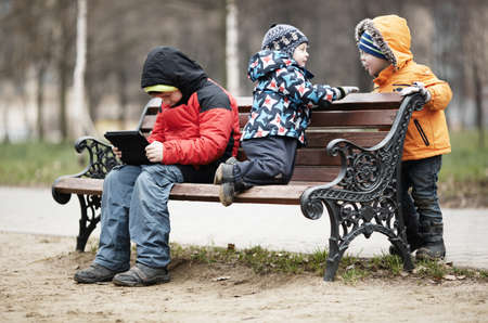 romp: Three young boys playing on a park bench in winter wrapped up warmly against the cold weather with one youngster reading a tablet as the two younger children romp around