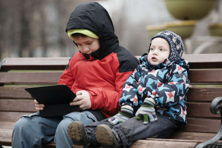 Young brothers sit together on a wooden park bench in warm winter clothing with the older child using a tablet computer photo