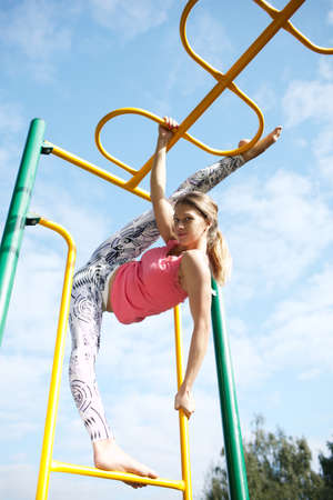 oudoors: Very supple athletic young woman playing on a brightly coloured metal frame opening her legs wide doing the splits as she hangs from the bars