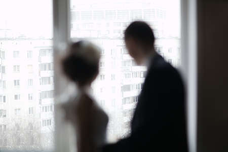 washed out: Bride and groom out of focus looking out the window. Washed out silhouettes. Romantic moments Stock Photo