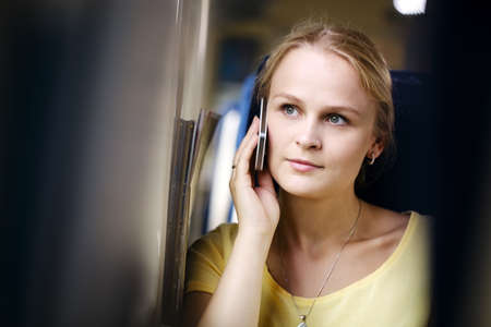 Attractive woman listening to a call on her mobile phone looking into the distance with a thoughtful expression while travelling by train Фото со стока