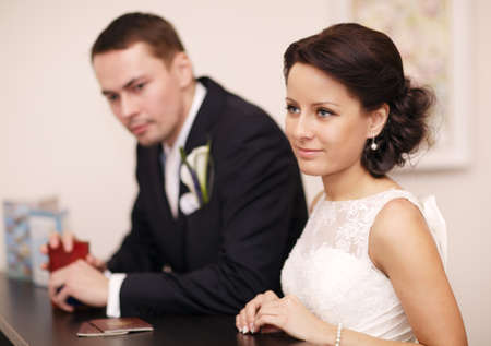 Elegant young couple standing at a reception desk with their passports with the beautiful woman smiling as she waits for service photo