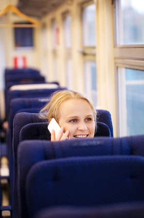 Young smiling woman traveling by train and talking on the phone. photo