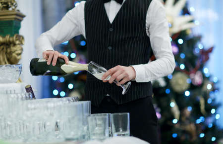 Waiter pouring glasses of champagne at a party or festive occasion with twinkling coloured lights in the background photo
