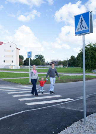 Mother, father and their little son crossing the road on crosswalk holding their hands. Stock Photo