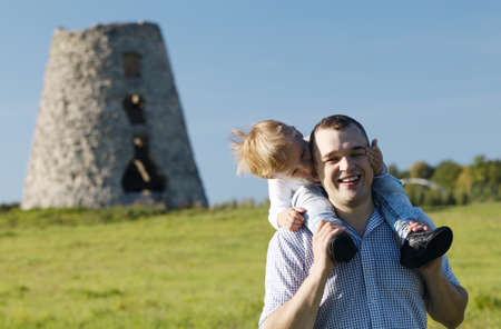 shoulder ride: Happy young father and son playing together in the countryside with the child riding piggy back on his dads shoulders on a clear sunny summer day Stock Photo