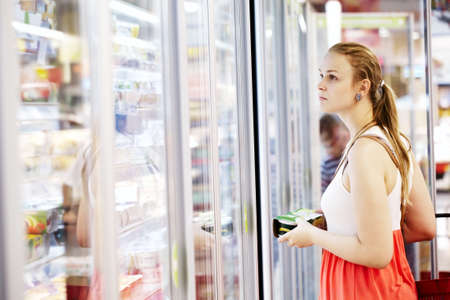 refrigerator with food: Young woman buying dairy or refrigerated groceries at the supermarket in the refrigerated section opening glass door of the fridge