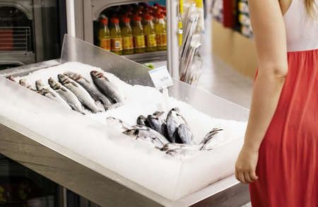 fish store: Woman shopping for fish in a supermarket standing looking at a display of fresh whole fish on ice